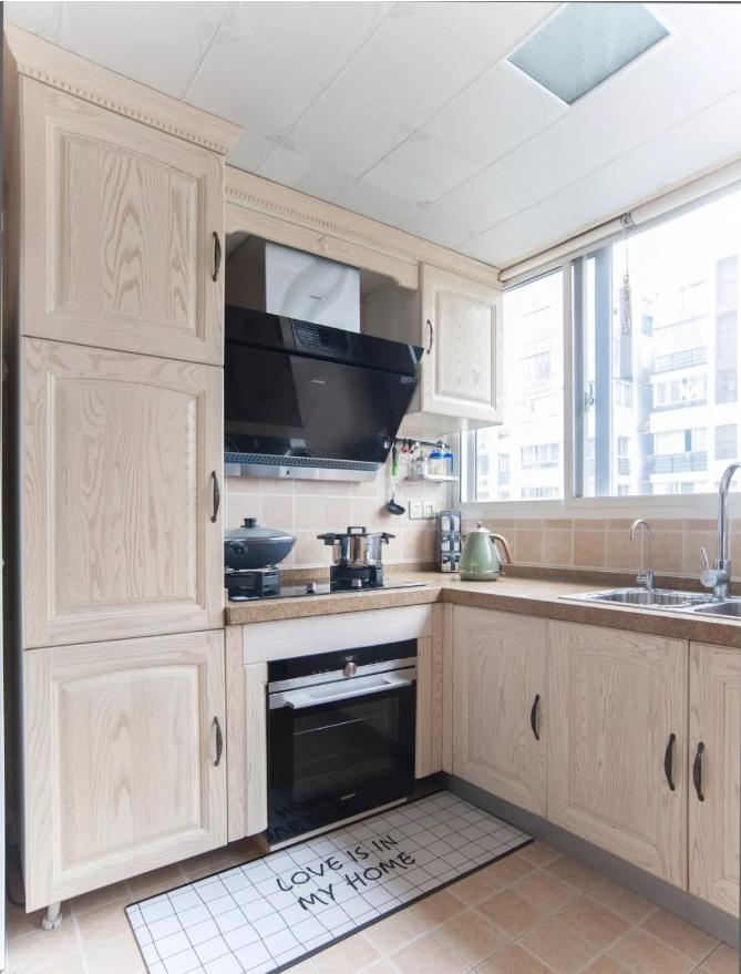 搭配定制木紋門片櫥柜,左側加高柜體方便收納各式廚房小家電,讓空間更