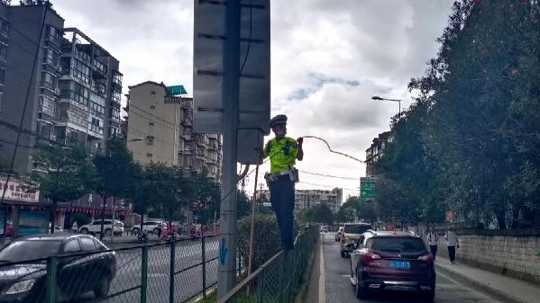 贵州贵阳:光缆掉落阻断交通 交警烈日下托举40分钟